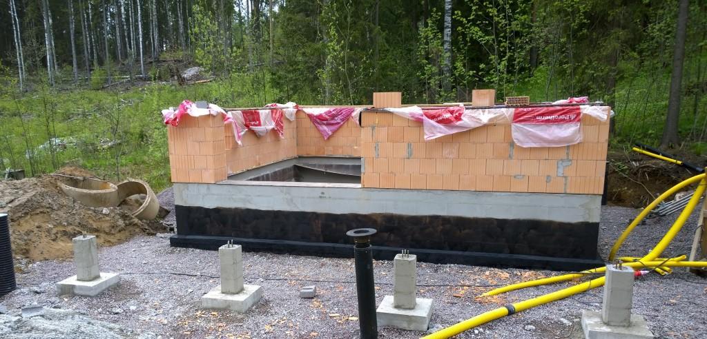 Saunalla bitumiprimeri sudittuna ja tolpat muurattuna.